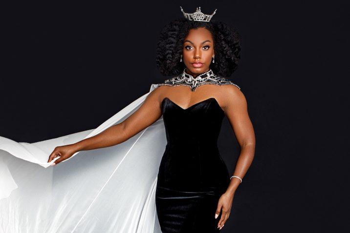 身穿黑色连衣裙,头戴白色斗篷,头戴皇冠的女人