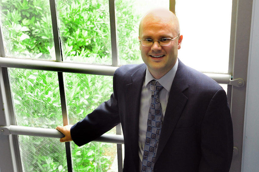 Dr. Brian Miller, wearing a blue suit and glasses, stands in front of window