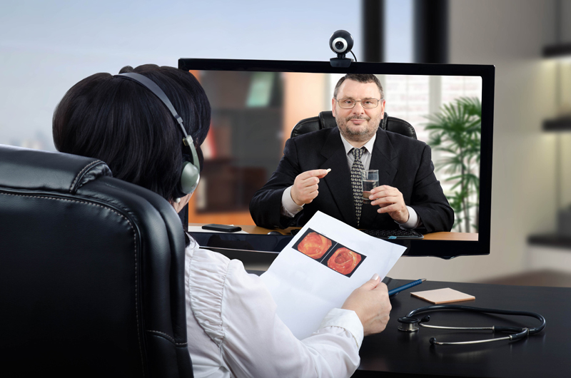 doctor speaking to man on computer