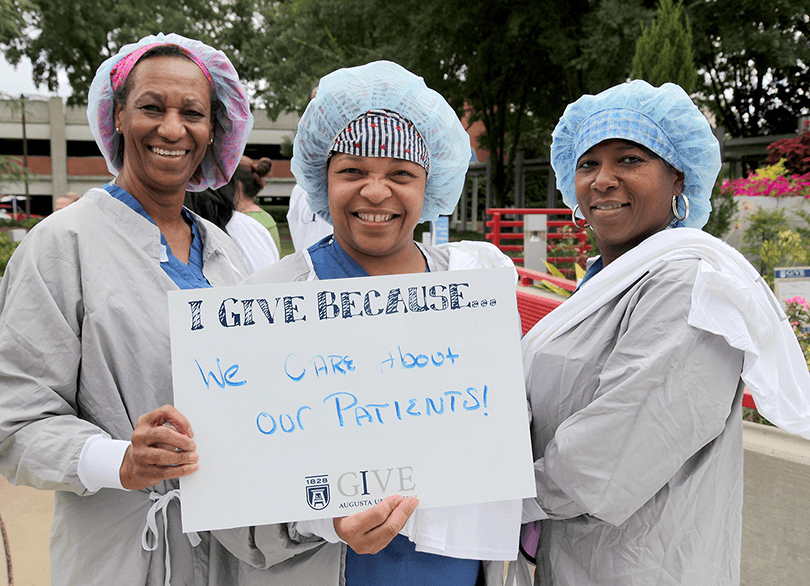 three woman nurses holding up a sign that says I give because we care about our patients
