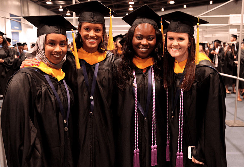 4 ladies in cap and gowns