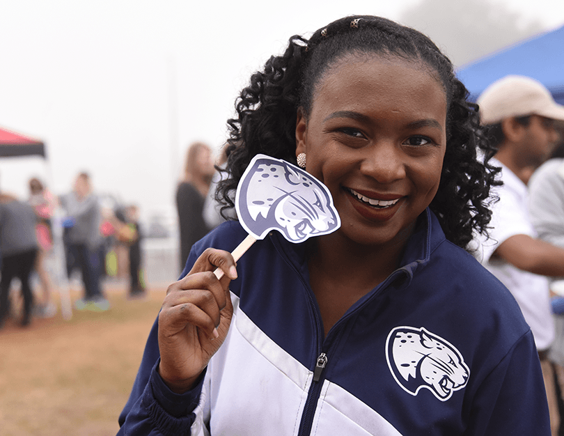 A lady holding a sign of Augusta University Jaguar head.