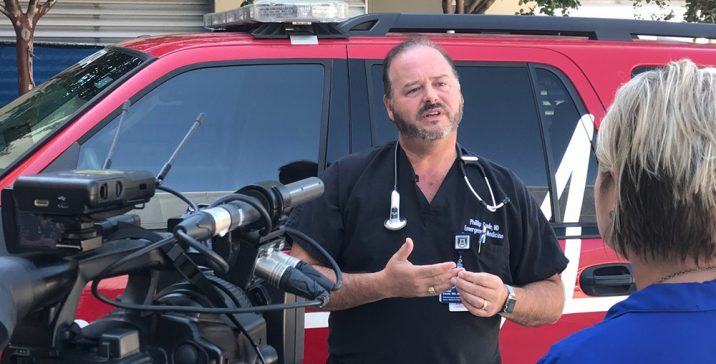 A man in hospital scrubs being interviewed by the media.