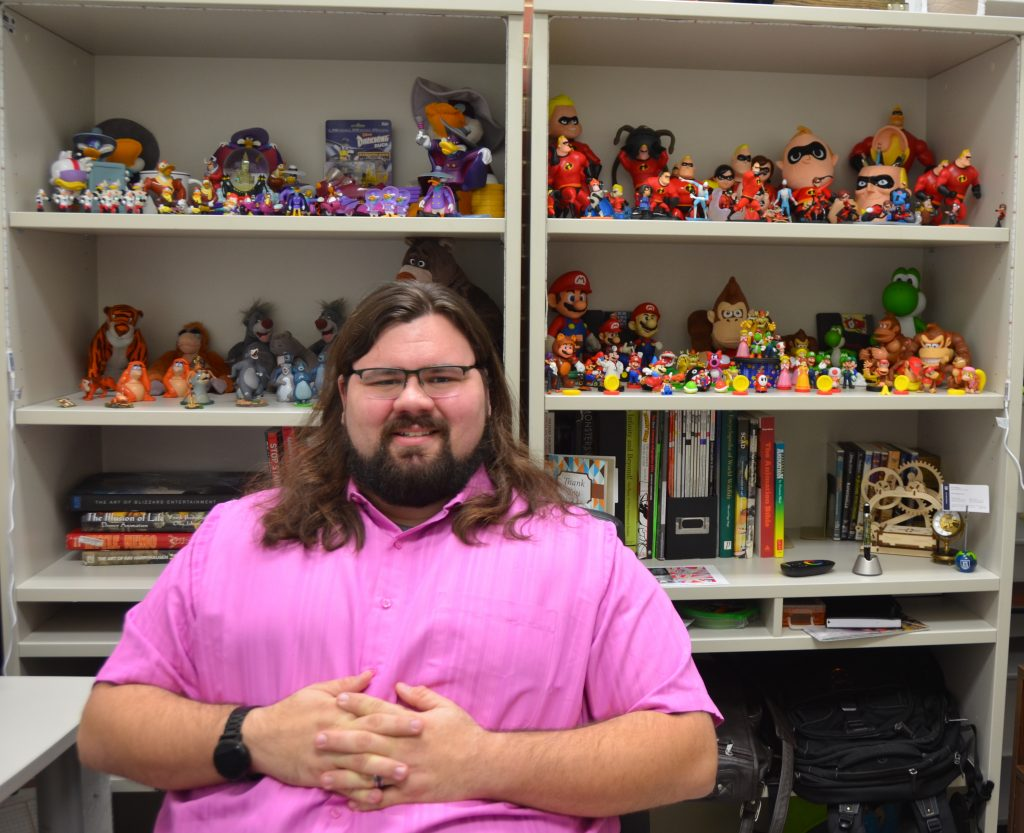 man sitting in front of action figures