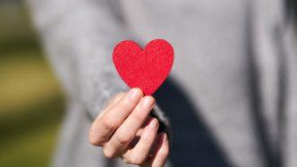 hands holding a paper cutout of a heart