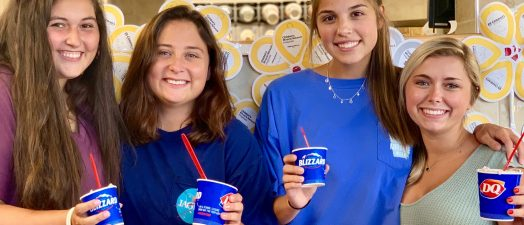 Four women posing with Dairy Queen Blizzards.