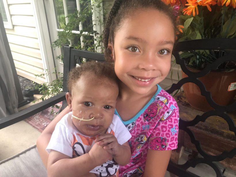 girl holding baby sister
