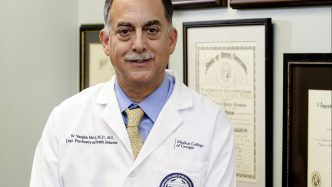 doctor in white coat sitting in front of plaques