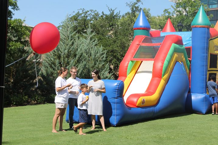 People standing in front of a bouncy slide