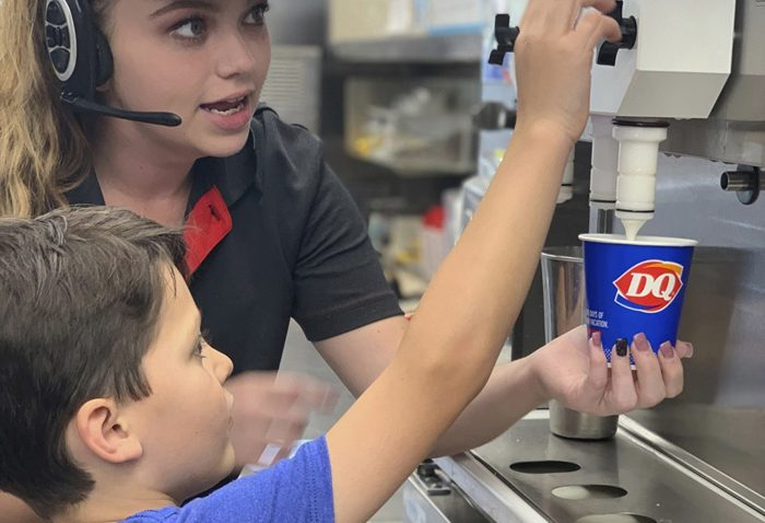 Dairy Queen employee helps boy at the ice cream machine.