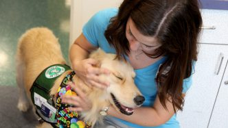 woman petting therapy dog while they smile