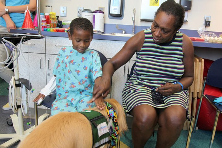 Mother and son petting therapy dog