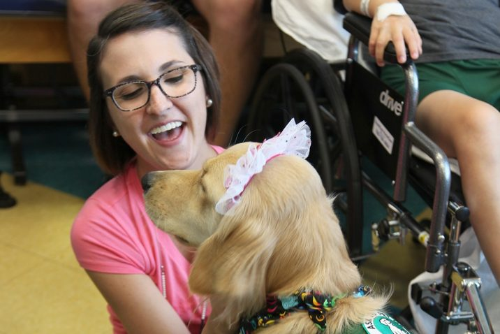 trainer smiling at therapy dog