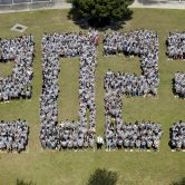 Students standing on a field in the shape of 2023