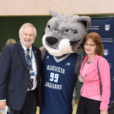 Two people standing with a mascot.