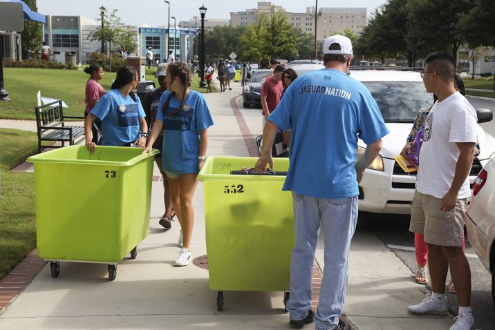 students rolling bins