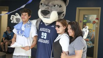 Mascot posing with a two women and a man.