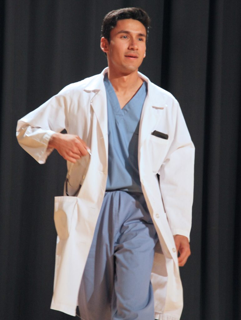 Man on stage with white coat.