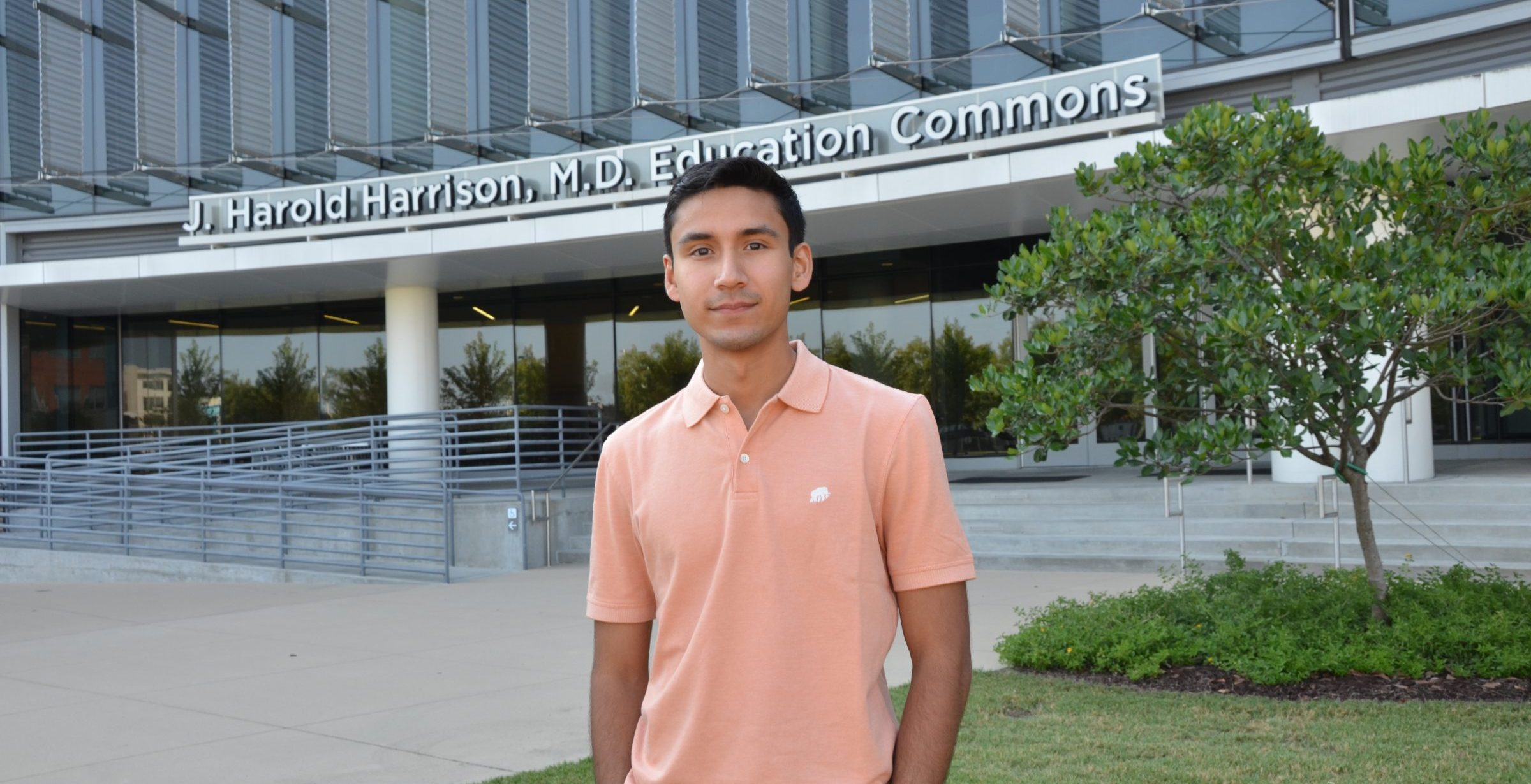 Student standing in front of building.