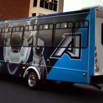 Color photo of Augusta University shuttle with mascot Augustus and the athletic A