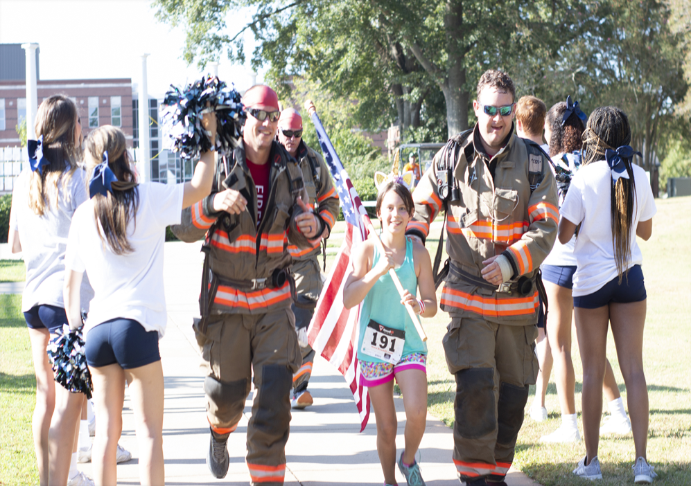 Two firefighters running with a flag.