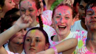 A group of girls smiling with paint on their faces.