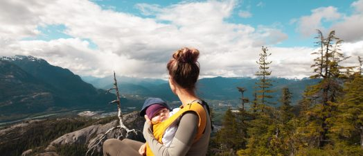 woman holding baby on top of mountain