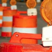 A line of orange and white construction barrels with orange lights on top