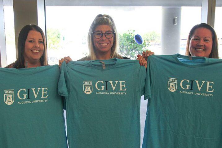 Three women holding up t-shirts