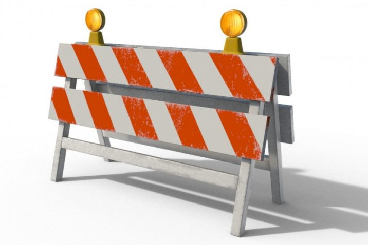color photo of construction barricades with orange and white stripes and two yellow lights on top