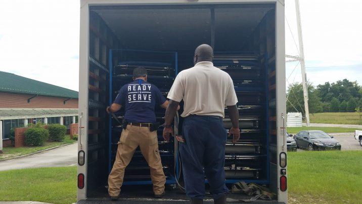 two men unloading truck full of supplies