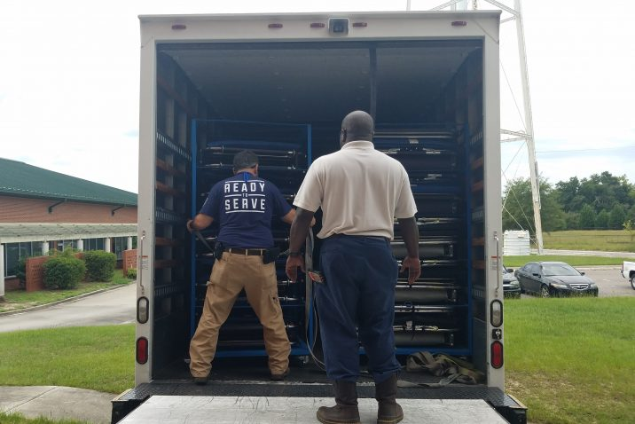 two men unloading truck full of supplies