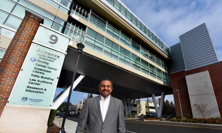 a doctor standing in front of the Georgia Cancer Center building.
