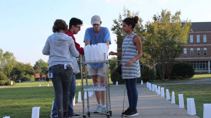 Four volunteers standing over a cart of paper luminary bags. The sidewalk they're standing on is lit on each side by the luminary bags they placed.
