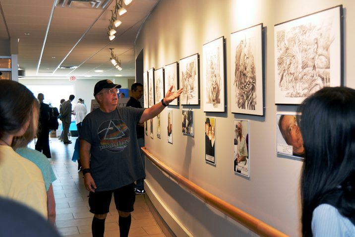 Man standing in front of sketches hanging on the wall.