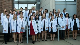 group photo of students with white coats