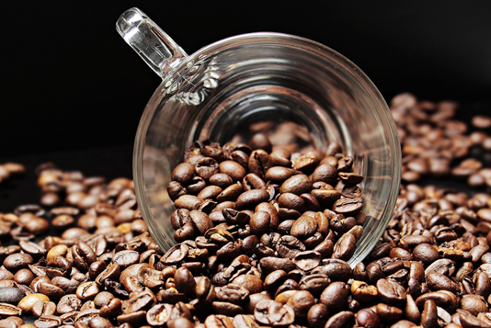 A cup surrounded by coffee beans.