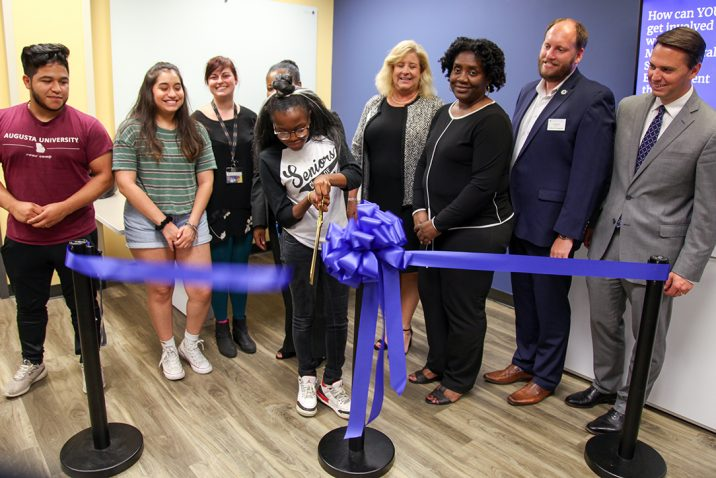 students gathering behind the ribbon cutting