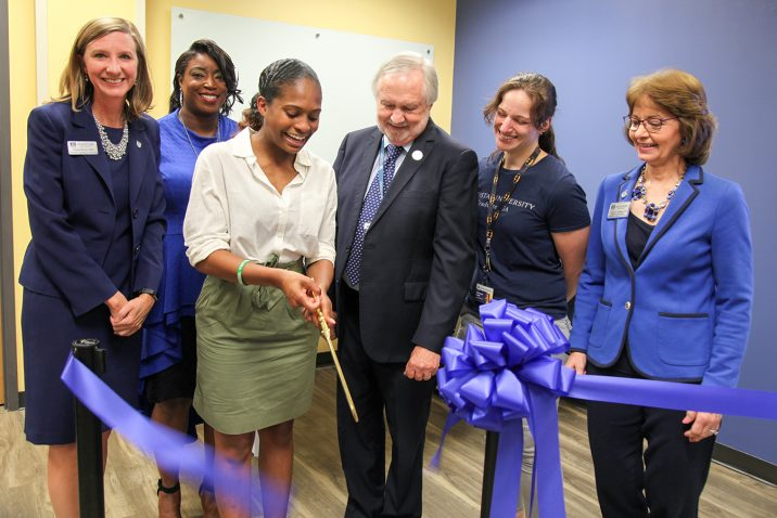 students and staff cutting the ribbon for the grand opening