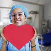 A nurse holding a heart-shaped paper.