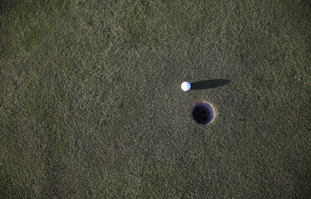 golf ball next to a golf hole