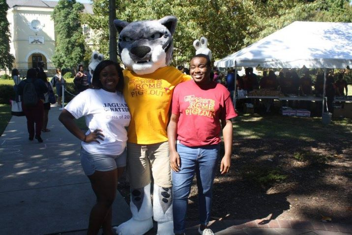 students smiling with the mascot