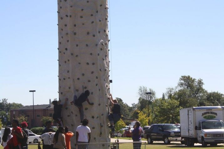 students climbing rock wall