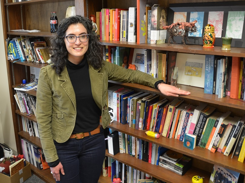 A woman standing by books.
