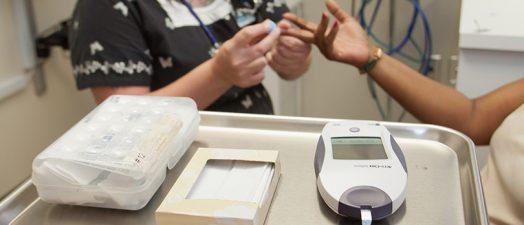 Nurse checking patients blood sugar.