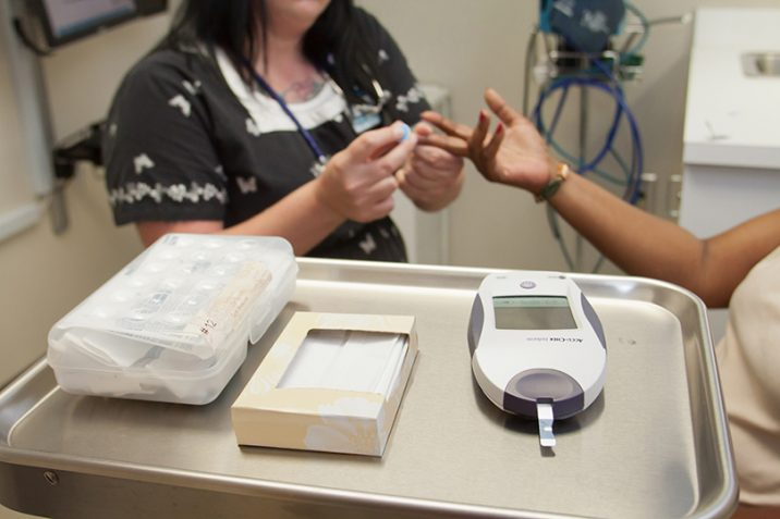 Nurse checking patients blood sugar.
