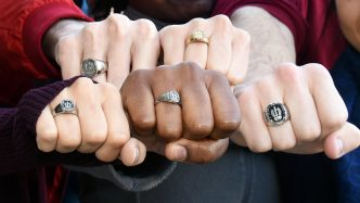 Five fists showing class rings