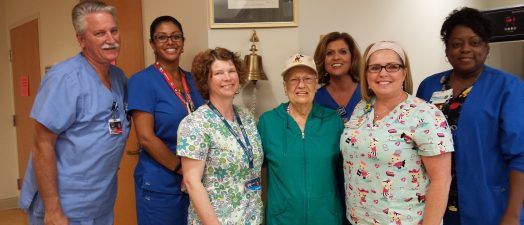 A woman surrounded by nursing staff at the Georgia Cancer Center