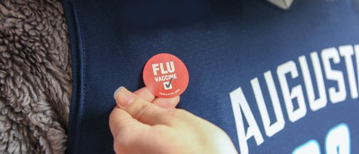 Image of red flu sticker on AU mascot Augustus's shirt