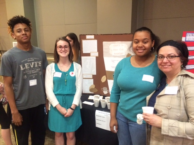 students smiling in front of poster presentation